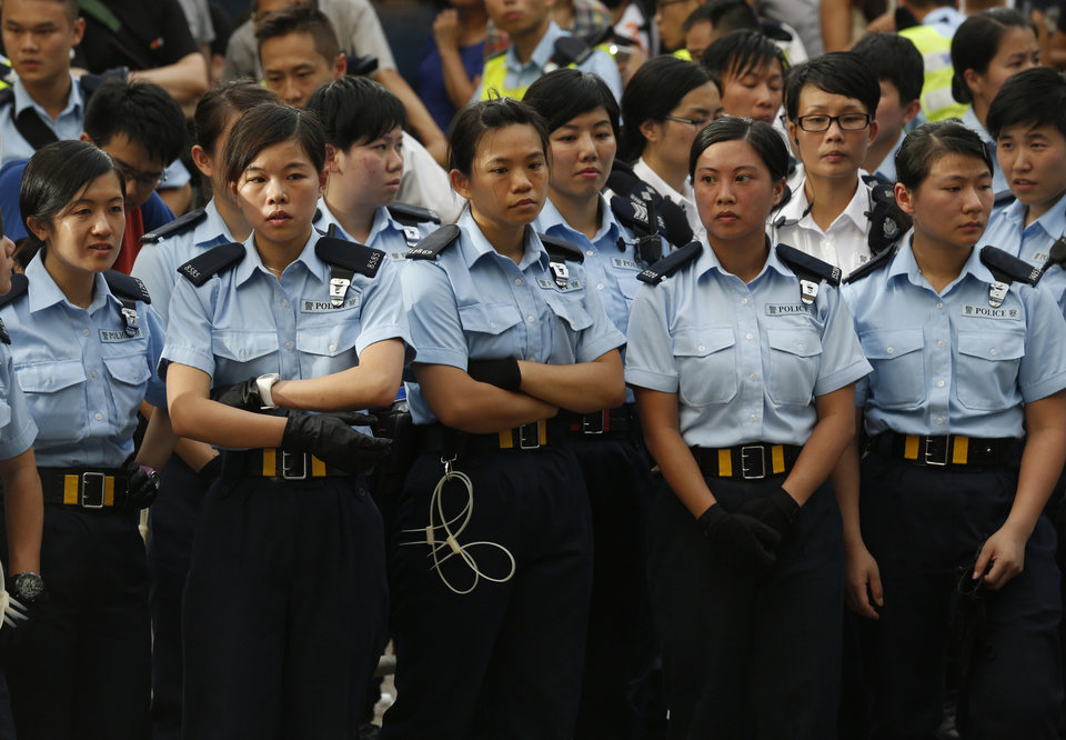 Photo - Policewomen stand next to the protesters during a peaceful sit-ins protest on a street in the financial district in Hong Kong Wednesday, July 2, 2014, following a huge rally to show their support for democratic reform and oppose Beijing's desire to have the final say on candidates for the chief executive's job. (AP Photo/Kin Cheung)