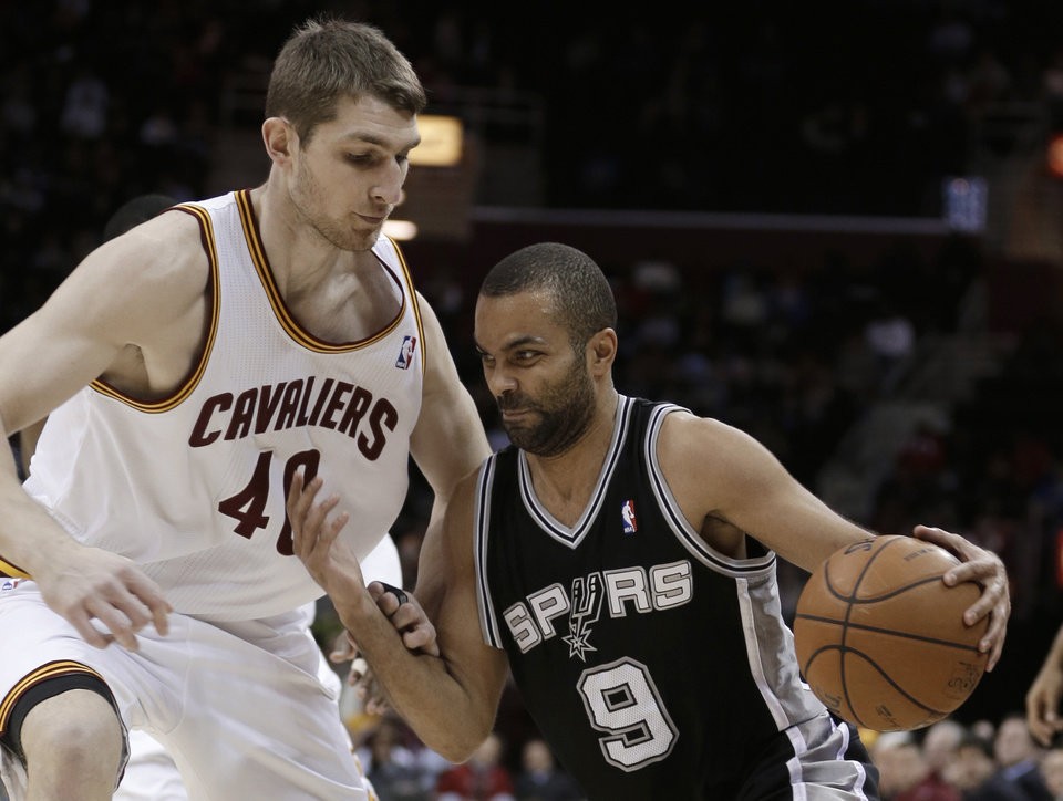 San Antonio Spurs' Tony Parker (9) drives past Cleveland Cavaliers' Tyler Zeller (40) during the first quarter of an NBA basketball game Wednesday, Feb. 13, 2013, in Cleveland. (AP Photo/Tony Dejak)