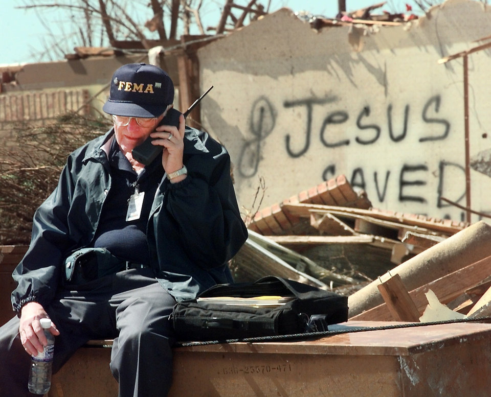 Tornado damage: FEMA worker Clem Chaffee talks on a cellular phone while waiting for President Clinton to arrive for a tour to view the damage in the Del Aire housing addition Saturday morning.