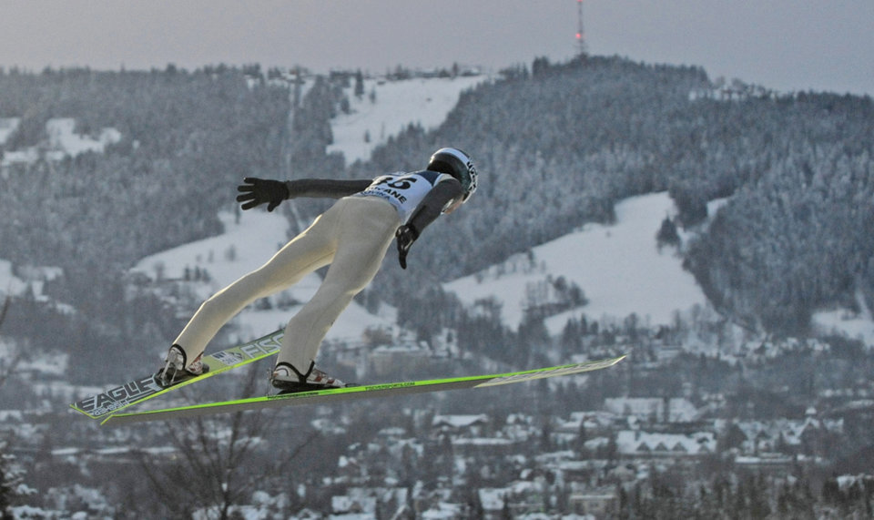 Photo - FILE - In this file photo taken Jan. 12, 2013, Austria's Michael Hayboeck is seen soaring through the air during the qualification round of the16th World Cup Ski Jumping competition, in Zakopane, Poland. Zakopane was to be one of the sites of the 2022 Winter Games that the nearby city of Krakow was bidding to co-host, but cancelled the effort the day after the residents voted against the plan in a local referendum on Sunday, May 25, 2014. (AP Photo/Alik Keplicz, file)