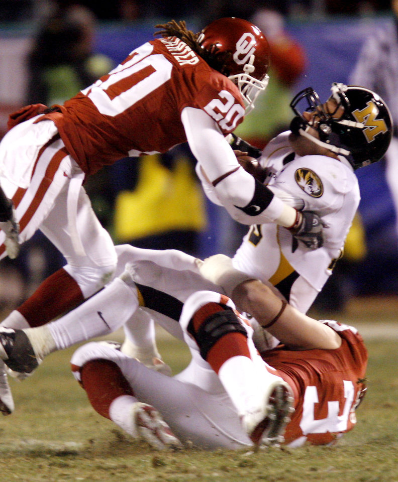 Photo - Oklahoma's Quinton Carter 920) and Austion English (33) bring down Missouri's Chase Daniel (10) during the first half of the Big 12 Championship college football game between the University of Oklahoma Sooners (OU) and the University of Missouri Tigers (MU) on Saturday, Dec. 6, 2008, at Arrowhead Stadium in Kansas City, Mo. 