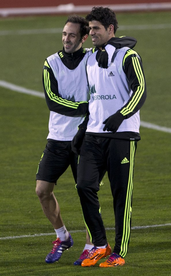 Photo - Spain's Diego Costa, right is hugged by Juanfran Torres during a training session in Madrid, Monday March 3, 2014. Spain will play Italy Wednesday in a friendly soccer match. (AP Photo/Paul White)
