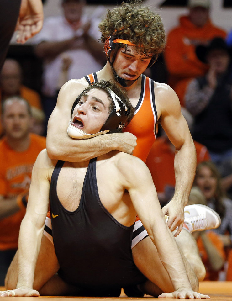 Photo - OSU's Daton Fix, top, wrestles Iowa's Austin DeSanto in a 133-pound match during a college wrestling dual between the Oklahoma State Cowboys and the Iowa Hawkeyes at Gallagher-Iba Arena in Stillwater, Okla., Sunday, Feb. 24, 2019. OSU won 27-12. Photo by Nate Billings, The Oklahoman