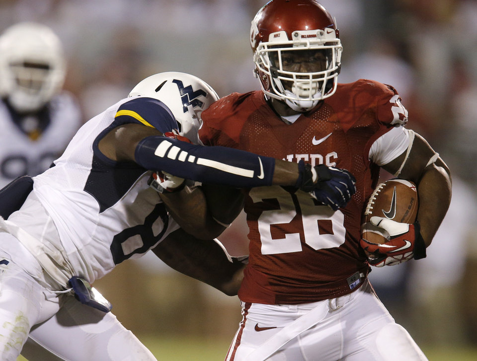 Photo - Oklahoma's Damien Williams (26) fights off West Virginia's Karl Joseph (8) during a college football game between the University of Oklahoma Sooners (OU) and the West Virginia University Mountaineers at Gaylord Family-Oklahoma Memorial Stadium in Norman, Okla., on Saturday, Sept. 7, 2013. Oklahoma won 16-7. Photo by Bryan Terry, The Oklahoman