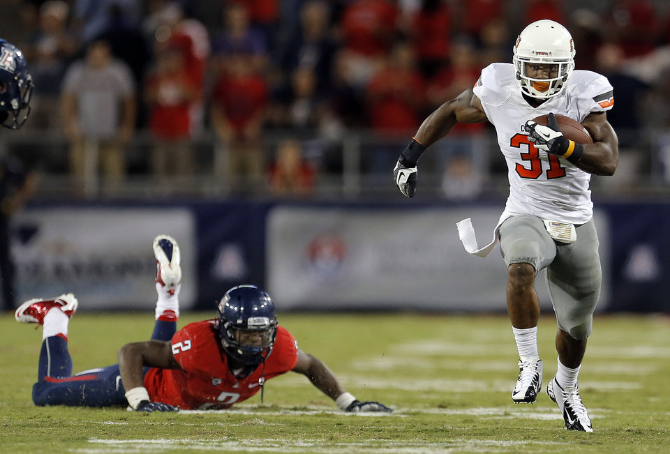 Oklahoma State\'s Jeremy Smith (31) gets past Arizona\'s Marquis Flowers (2) during the college football game between the University of Arizona and Oklahoma State University at Arizona Stadium in Tucson, Ariz., Saturday, Sept. 8, 2012. Photo by Sarah Phipps, The Oklahoman