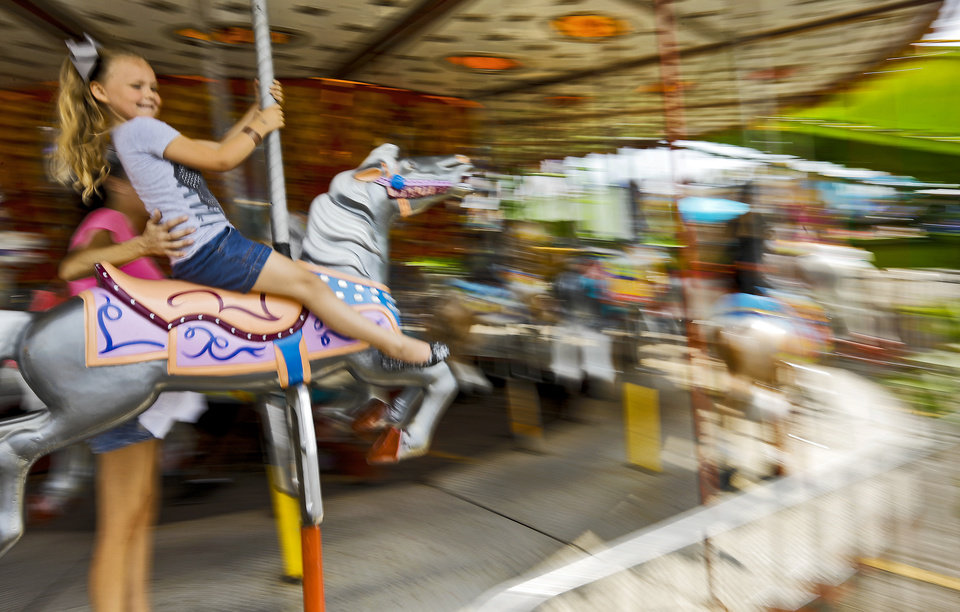 Photo - Victoria Powell,5, of Oklahoma City, is a blur of motion as she rides the carousel during the 2013 Oklahoma State Fair on Monday, Sep. 16, 2013. Photo by Chris Landsberger, The Oklahoman