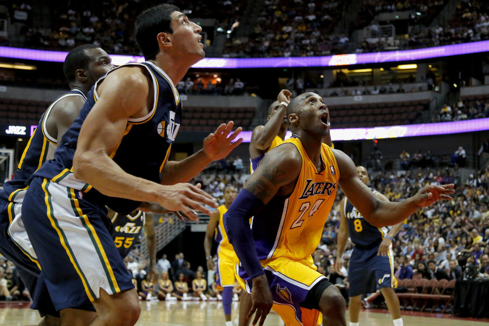 Photo -   Los Angeles Lakers' Kobe Bryant, right, and Utah Jazz's Enes Kanter look at the ball in the first half of an NBA preseason basketball game in Anaheim, Calif., Tuesday, Oct. 16, 2012. (AP Photo/Jae Hong)