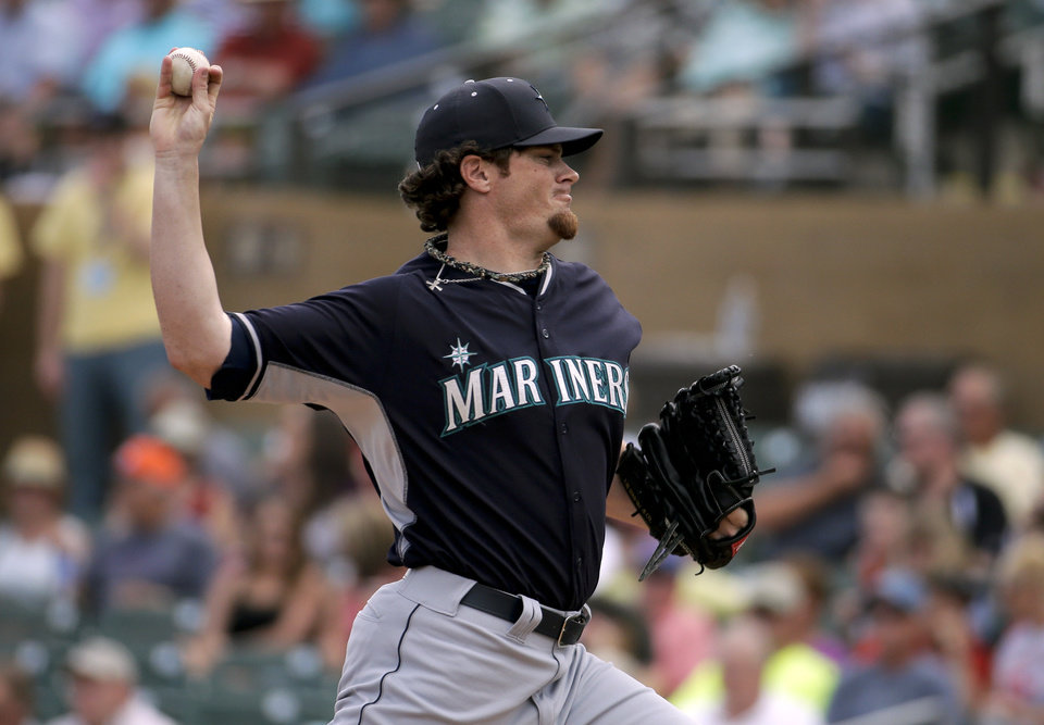 Photo - Seattle Mariners starting pitcher Blake Beavan throws against the Arizona Diamondbacks during the first inning of a spring exhibition baseball game in Scottsdale, Ariz., Thursday, March 13, 2014. (AP Photo/Chris Carlson)