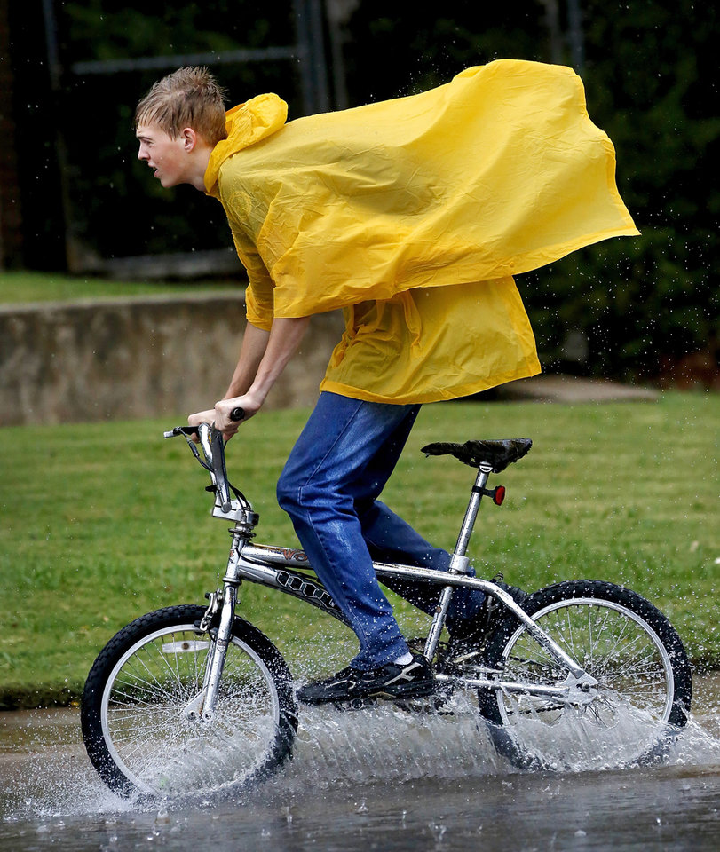 Zachary Ziegert has only a poncho to protect him from the rain as he pedals along NE 63 near the Broadway Extension Saturday. Strong thunderstorms, producing heavy downpours and lightning moved through the Oklahoma City area  during the morning and early afternoon hours on Saturday, Oct. 13, 2012. Overcast skies and intermittent rain continued throughout the day.    Photo by Jim Beckel, The Oklahoman