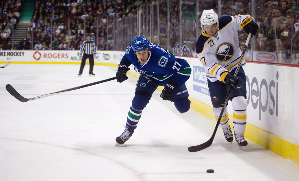 Photo - Vancouver Canucks' Shawn Matthias, left, chases after Buffalo Sabres' Matt D'Agostini as he plays the puck during first period NHL hockey action in Vancouver, British Columbia, on Sunday March 23, 2014. (AP Photo/The Canadian Press, Darryl Dyck)