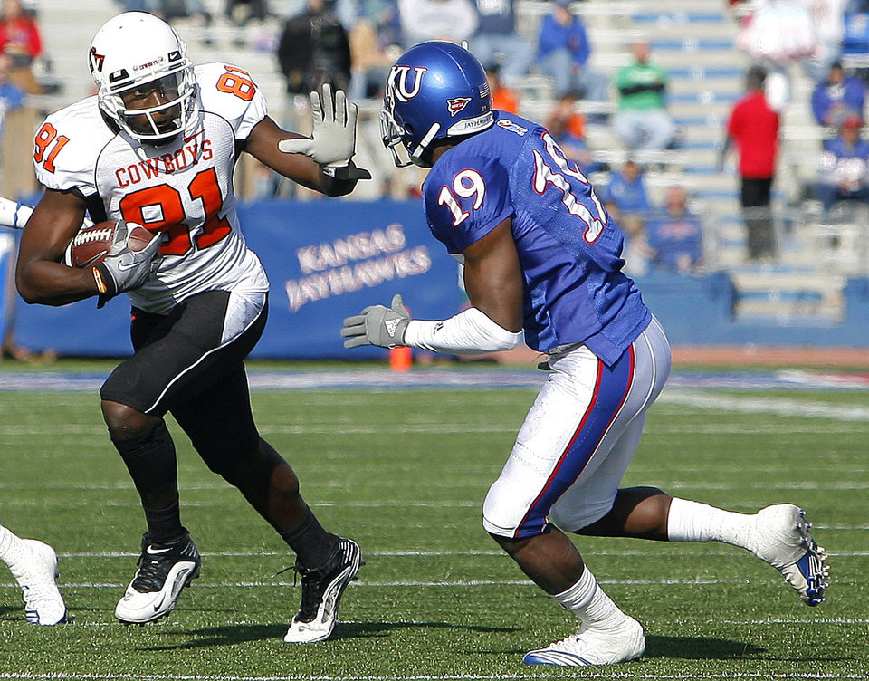 Photo - Oklahoma State's Justin Blackmon (81) looks to get past Kansas' Isiah Barfield (19) during the college football game between Oklahoma State (OSU) and Kansas (KU), Saturday, Nov. 20, 2010 at Memorial Stadium in Lawrence, Kan. Photo by Sarah Phipps, The Oklahoman