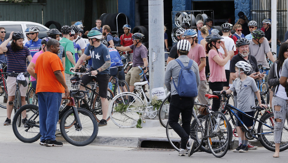 Photo - Dozens of bicyclists ride along Classen Boulevard Tuesday, May 7, 2019, to highlight the need for better bike lanes, stopping at 16th and Classen Blvd. where a ghost bike memorial for Chad Epley who was killed at the intersection while riding home after work.  Photo by Doug Hoke.