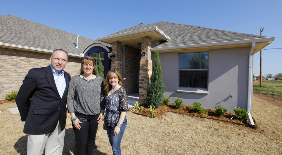 """Photo - Homebuilder Jay Evans of Two Structures Homes, with wife Tricia Evans and daughter Kelsey Evans, outside the """"House of Hope"""" fundraiser home at 841 SW 11 in Moore. It will be featured in the Parade of Homes Spring Festival, with homes open 1 to 7 p.m. May 2-4 and May 9-11.  Photos by Paul B. Southerland, The Oklahoman  PAUL B. SOUTHERLAND -  PAUL B. SOUTHERLAND"""
