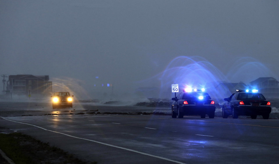 Photo - Police watch a flooded area as a vehicle navigates Highway 64 as wind pushes water over the road while Hurricane Arthur passes through Nags Head, N.C., Friday, July 4, 2014. (AP Photo/Gerry Broome)