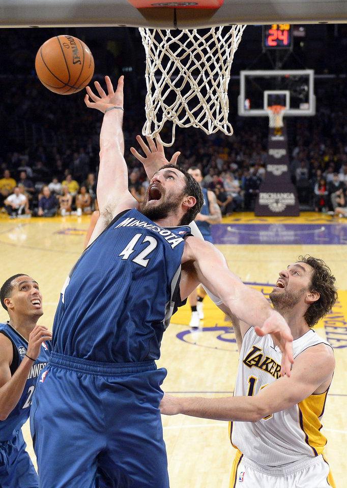 Photo - Minnesota Timberwolves forward Kevin Love, left, goes after a rebound along with Los Angeles Lakers center Pau Gasol, of Spain, during the first half of an NBA basketball game Sunday, Nov. 10, 2013, in Los Angeles. (AP Photo/Mark J. Terrill)