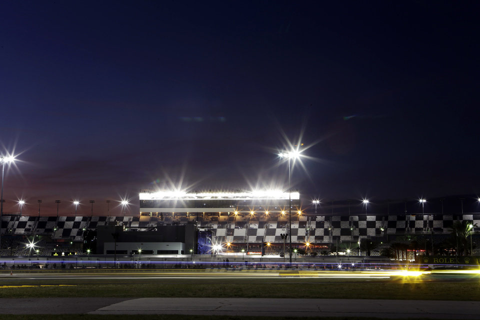 Photo - Car headlights streak through a horseshoe turn during the Grand-Am Series Rolex 24 hour auto race at Daytona International Speedway, Saturday, Jan. 26, 2013, in Daytona Beach, Fla. (AP Photo/John Raoux)