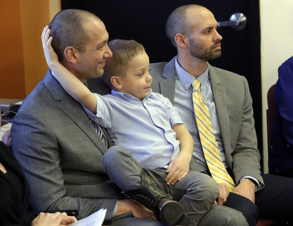 Photo - Plaintiffs Matthew Barraza, left, and his husband Tony Milner, right, look on as they hold their son Jesse, 4, during a news conference, Tuesday, Jan. 21, 2014, in Salt Lake City. The American Civil Liberties Union has sued the state of Utah over the issue of gay marriage, saying the official decision to stop granting benefits for newly married same-sex couples has created wrenching uncertainty. The lawsuit filed Tuesday said the state has put hundreds of gay and lesbian couples in legal limbo and prevented them from getting key protections for themselves and their children. (AP Photo/Rick Bowmer)