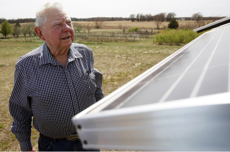 Photo -  Herb Hill, 85, looks at the solar panels he installed at his home in Crescent. Hill has 36 solar panels that supplement his electricity use. Photo by KT King, The Oklahoman    KT King -