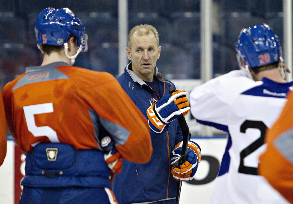Edmonton Oilers coach Ralph Krueger talks with Ladislav Smid, left, and Eric Belanger during the NHL hockey team's training camp in Edmonton, Alberta, on Monday, Jan. 14, 2013. (AP Photo/The Canadian Press, Jason Franson)