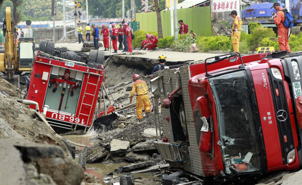 Photo - Rescue workers use a sniffer dog to look for missing persons believed to be buried as firetrucks lie damaged after massive gas explosions in Kaohsiung, Taiwan, Friday, Aug. 1, 2014. A series of explosions about midnight Thursday and early Friday ripped through Taiwan's second-largest city, killing scores of people, Taiwan's National Fire Agency said Friday. (AP Photo/Wally Santana)
