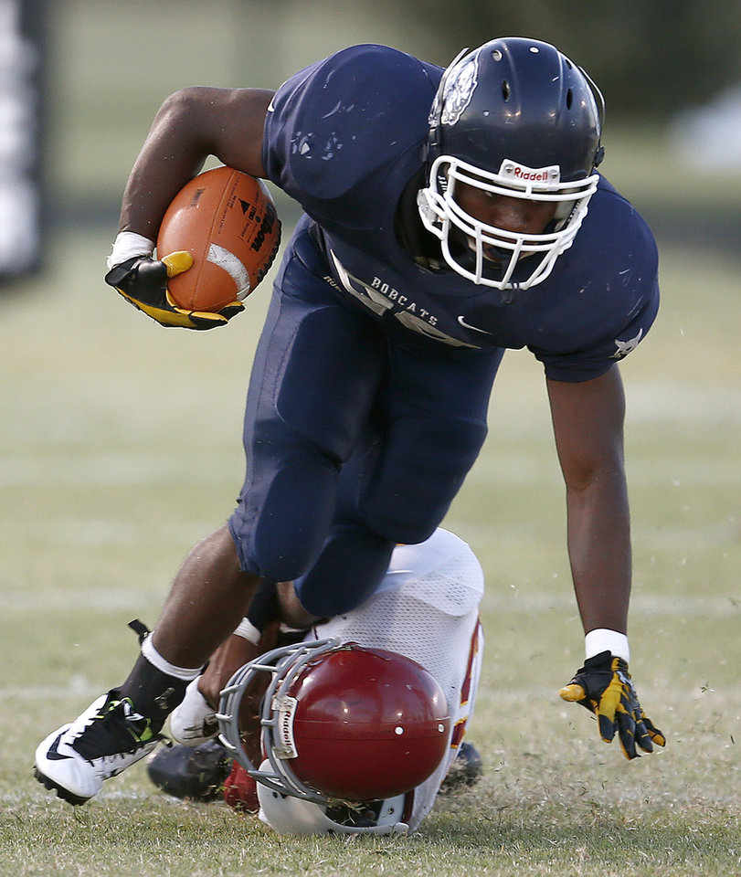 Photo - Star Spencer's Malik Livingston runs past Centennial's Steven Perry during the  All-City Preview football scrimmages at Douglass High School in Oklahoma City, Friday, August 29, 2014. Photo by Bryan Terry, The Oklahoman