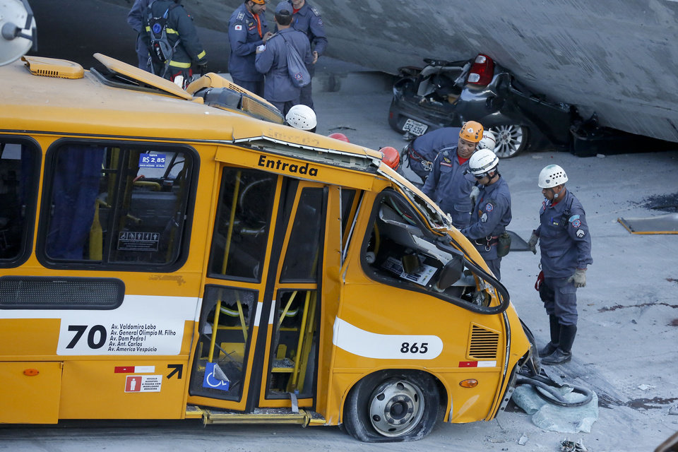 Photo - Fire department personnel work to retrieve a body from a bus after retrieving it from underneath a collapsed bridge in Belo Horizonte, Brazil, Thursday, July 3, 2014. The overpass under construction collapsed Thursday in the Brazilian World Cup host city. The incident took place on a main avenue, the expansion of which was part of the World Cup infrastructure plan but, like most urban mobility projects related to the Cup, was not finished on time for the event. (AP Photo/Victor R. Caivano)