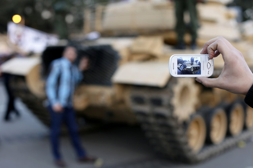 An Egyptian protester takes a picture with his mobile of a friend in front of an Egyptian army tank outside the presidential palace, background, in Cairo, Egypt, Saturday, Dec. 8, 2012. Egypt's military warned Saturday of 'disastrous consequences' if the crisis that sent tens of thousands of protesters back into the streets is not resolved, signaling the army's return to an increasingly polarized and violent political scene.(AP Photo/Hassan Ammar)
