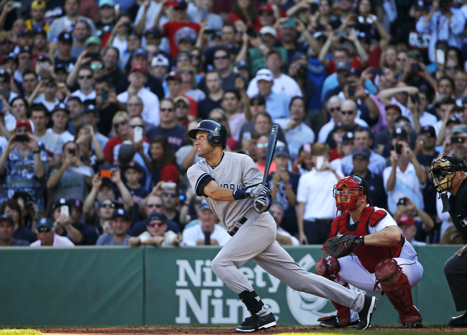 Photo - New York Yankees designated hitter Derek Jeter follows through on a single in the third inning against the Boston Red Sox in a baseball game Sunday, Sept. 28, 2014, in Boston. It is the last baseball game of Jeter's career. (AP Photo/Elise Amendola)