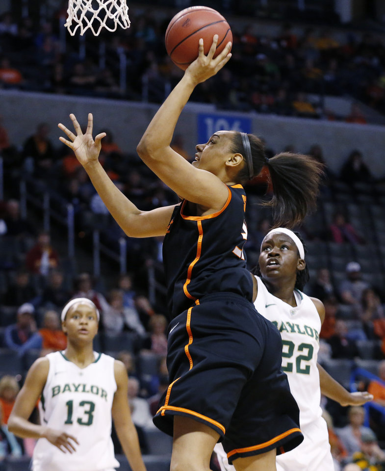 Oklahoma State center Kendra Suttles, center, shoots in front of Baylor forward Nina Davis (13) and point Sune Agbuke (22) in the first half of an NCAA college basketball game in the semifinals of the Big 12 Conference women\'s college tournament in Oklahoma City, Sunday, March 9, 2014. Baylor won 65-61. (AP Photo/Sue Ogrocki)