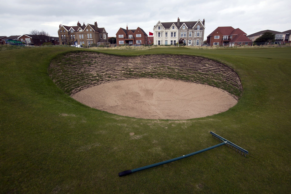 Photo - FILE - In this April 23, 2014, file photo, a rake rests next to a bunker on the first hole at Royal Liverpool Golf Club in Hoylake, England. The British Open golf championship begins on Thursday July 17, 2014. (AP Photo/Jon Super, File)