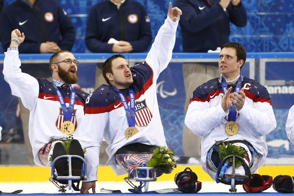 Photo - United States players Taylor Lipsett, left, Greg Shaw, center, and Andy Yohe celebrate after winning the gold medal ice sledge hockey match against Russia at the 2014 Winter Paralympics in Sochi, Russia, Saturday, March 15, 2014. United States won 1-0. (AP Photo/Pavel Golovkin)