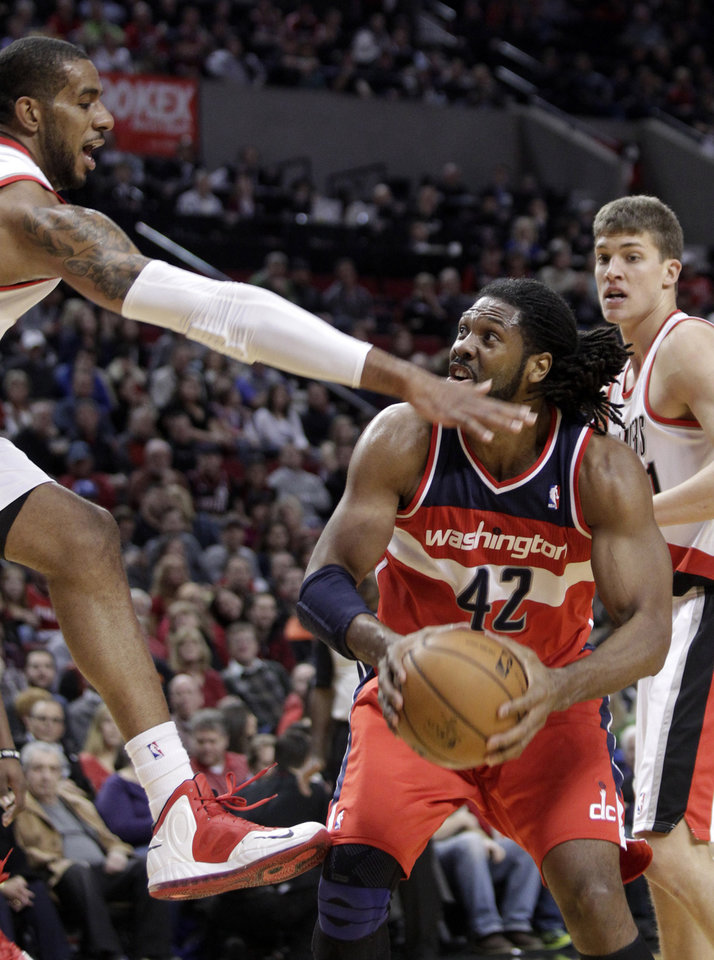 Washington Wizards forward Nene (42) looks to shoot against Portland Trail Blazers forward LaMarcus Aldridge during the first quarter of an NBA basketball game in Portland, Ore., Monday, Jan. 21, 2013. Trail Blazers center Meyers Leonard is at rear. (AP Photo/Don Ryan)