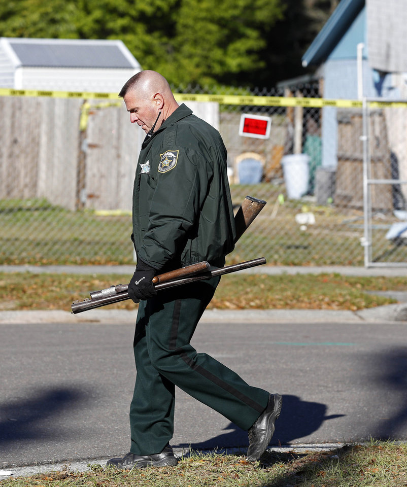 Photo - Hillsborough Sheriff Deputy removes two rifles that were recovered from the home of Jeff Bush,  as it is destroyed, Monday, March 4, 2013 in Seffner, Fla.  A sinkhole opened up underneath the house late Thursday, Feb. 28, 2013, swallowing Bush, 37.  The 20-foot-wide opening of the sinkhole was almost covered by the house, and rescuers said there were no signs of life since the hole opened Thursday night.  (AP Photo/Scott Iskowitz)