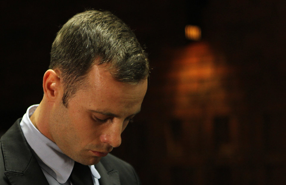 Photo - Olympic athlete Oscar Pistorius stands inside the court as a police officer looks on during his bail hearing at the magistrate court in Pretoria, South Africa, Wednesday, Feb. 20, 2013. A South African judge says defense lawyers will need to offer