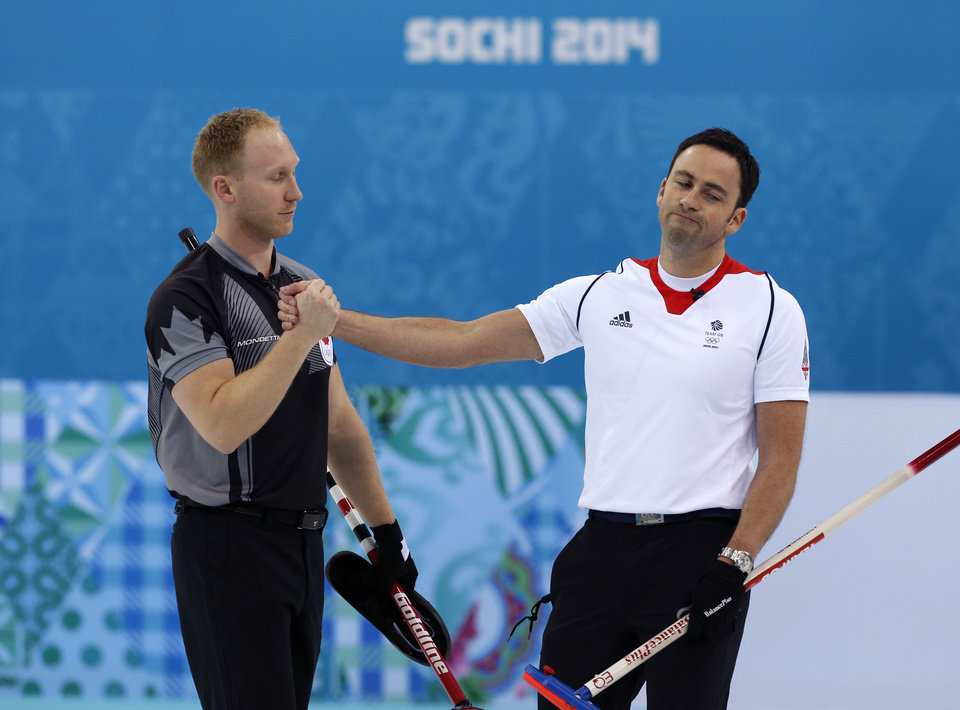 Photo - Canada's skip Brad Jacob, left, shakes Britain skip David Murdoch's hand after defeating his team in the men's curling gold medal game at the 2014 Winter Olympics, Friday, Feb. 21, 2014, in Sochi, Russia. (AP Photo/Robert F. Bukaty)