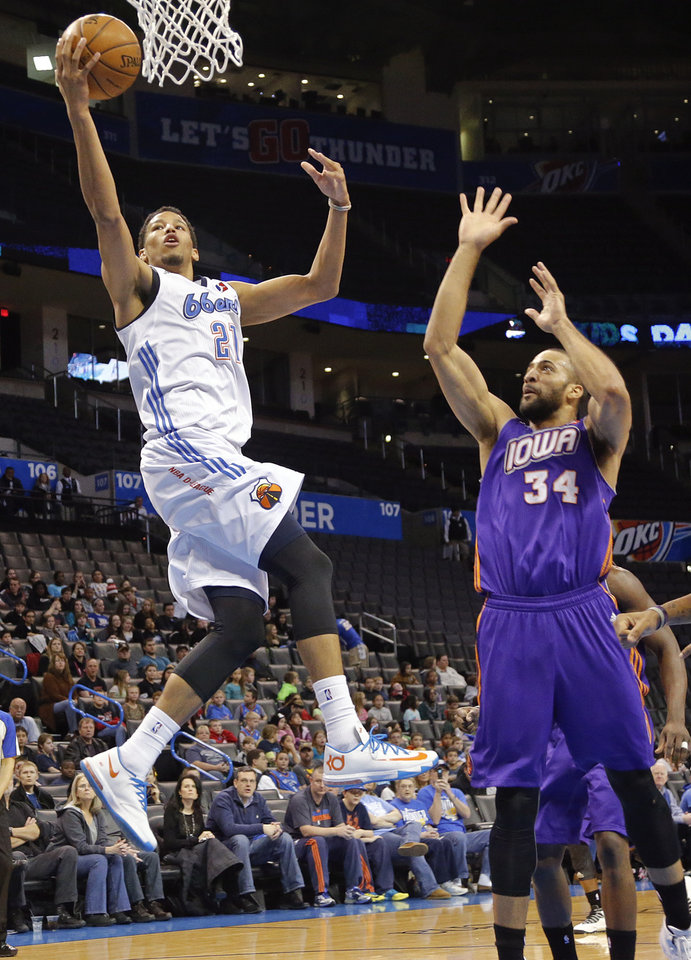 Photo - Tulsa's Andre Roberson (21) drives to the basket past Iowa's Jackie Carmichael (34) during the NBA Developmental game between the Tulsa 66ers and the Iowa Energy at the Chesapeake Energy Arena in Oklahoma City, Okla. on Tuesday, Feb. 4, 2014. Photo by Chris Landsberger, The Oklahoman