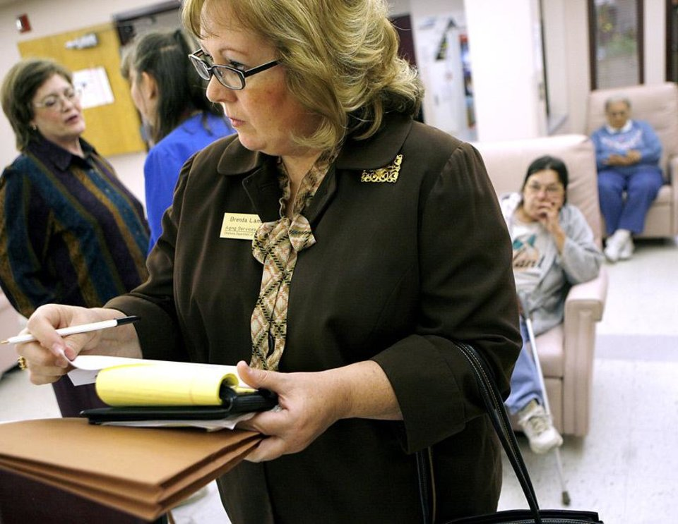 Photo - Brenda Lambeth, of DHS, takes notes during a monitoring visit at Eastern Oklahoma County Tech's Senior Adult Day Center on Thursday, Nov. 12, 2009. By John Clanton, The Oklahoman