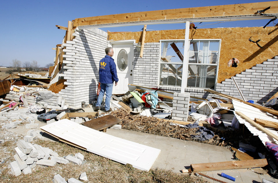 Photo - Rick Smith, warning coordination meteorologist, National Weather Service Forecast Office, Norman, looking at house damage to rate the tornado intensity on Brock Road in Lone Grove, Wednesday, Feb. 11, 2009.  BY PAUL B. SOUTHERLAND, THE OKLAHOMAN