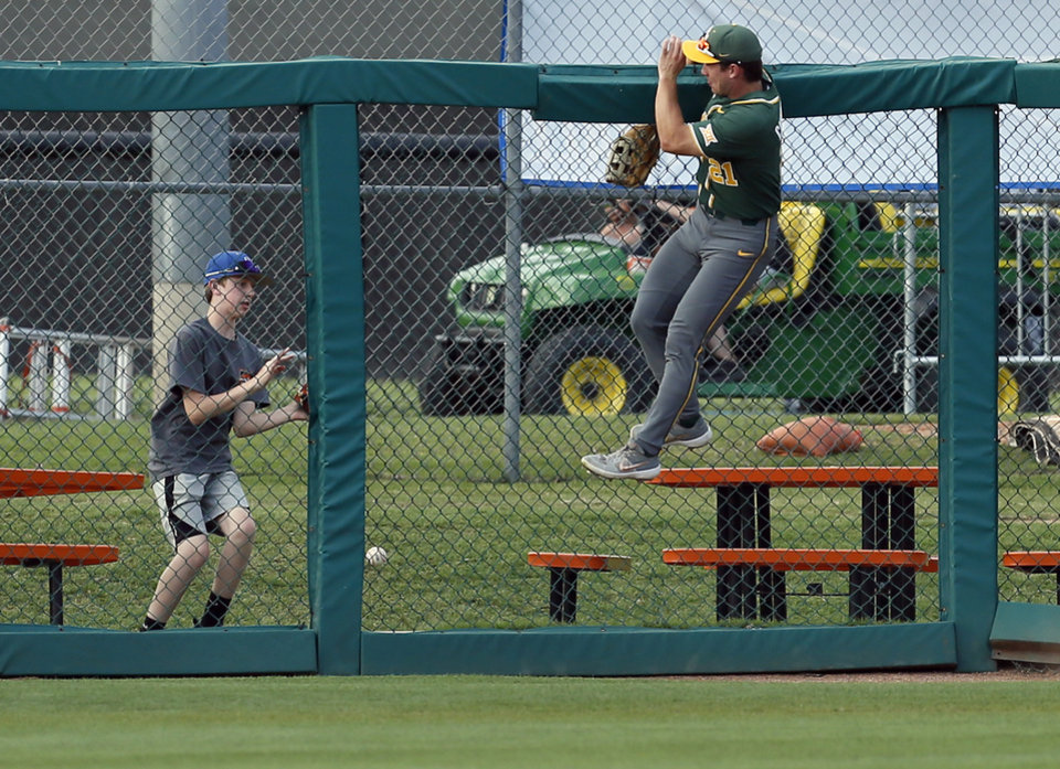 Photo - Baylor center fielder Richard Cunningham (21) hangs on the outfield fence as a home run by OSU's Trevor Boone, not pictured, falls in front of a fan in the second inning during a college baseball game between Baylor and Oklahoma State in the last regular-season series at Allie P. Reynolds Stadium in Stillwater, Okla., Friday, May 17, 2019. [Nate Billings/The Oklahoman]