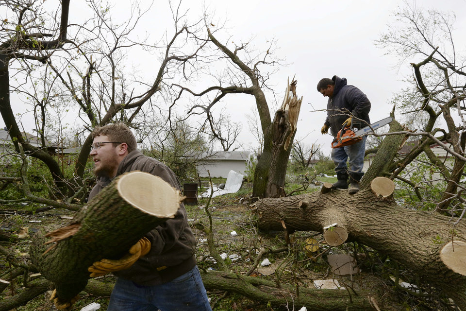 Photo - Adam Pankoke, left, and Nick Streit, clear fallen trees in Beaver Crossing, Neb., Monday, May 12, 2014. Beaver Crossing was hit hard after several tornadoes moved across Nebraska on Sunday causing damage to homes and businesses in or near Sutton, Garland, Cordova and Daykin. The storms also left more than 18,000 utility customers without electricity. (AP Photo/Nati Harnik)