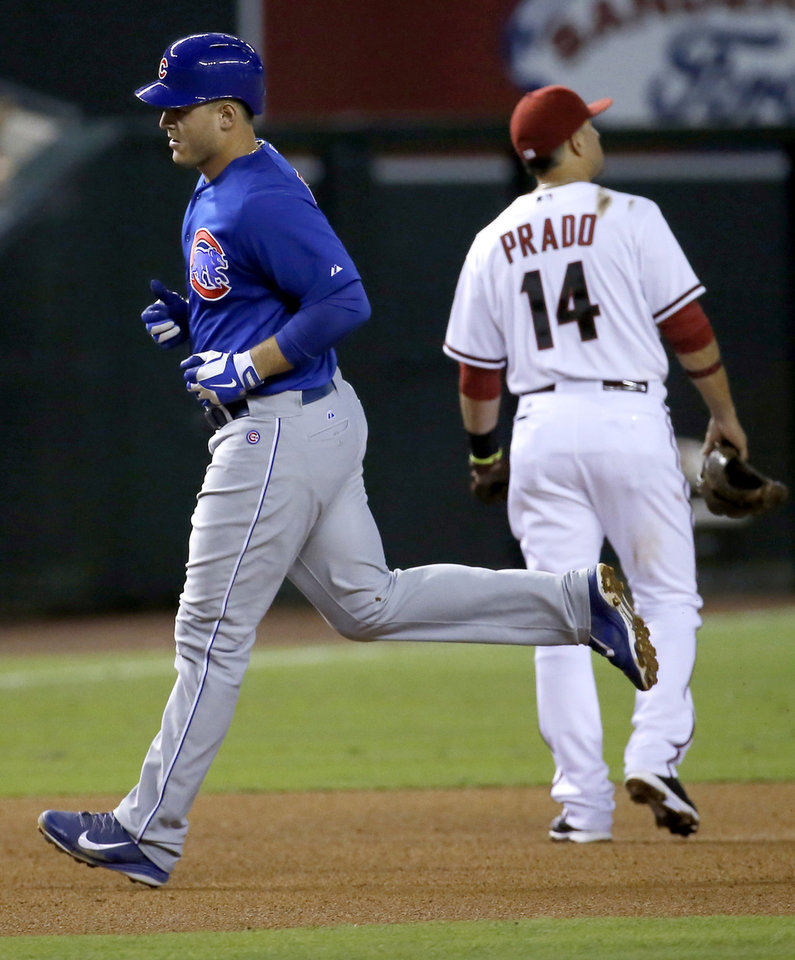 Photo - Chicago Cubs' Anthony Rizzo rounds the bases after hitting a two run home run as Arizona Diamondbacks' Martin Prado walks away during the fourth inning of a baseball game, Friday, July 18, 2014, in Phoenix. (AP Photo/Matt York)