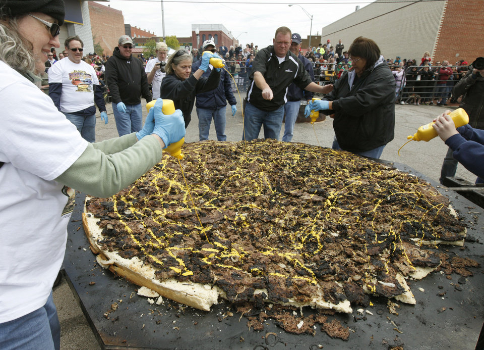 Ladies spread mustard onto an enormous hamburger during the Fabulous Burger Day Festival in El Reno, OK, Saturday, May 4, 2013,  By Paul Hellstern, The Oklahoman