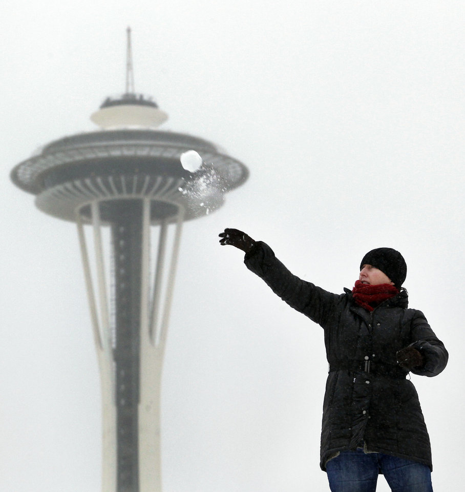 FILE - In this Jan. 18, 2012 file photo, the the Space Needle is shown in the background as Lynne Wyllie tosses a snowball in a downtown Seattle park. With 2013\'s winter half-over and mild weather holding for Seattle, the city could make it through the season without a significant snowfall. Meteorologist Johnny Burg said said Monday, Feb. 11, 2013, that Seattle typically goes without winter snow only once or twice a decade. (AP Photo/Elaine Thompson, File)