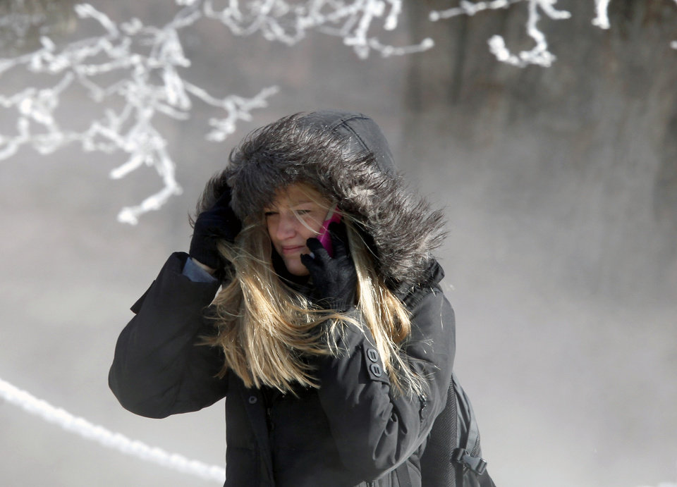 Photo - University of Wisconsin-Madison student Marisa Weich contends with sub-zero wind chill temperatures while making her way to class on the campus Tuesday, Jan. 22, 2013. (AP Photo/Wisconsin State Journal, John Hart)