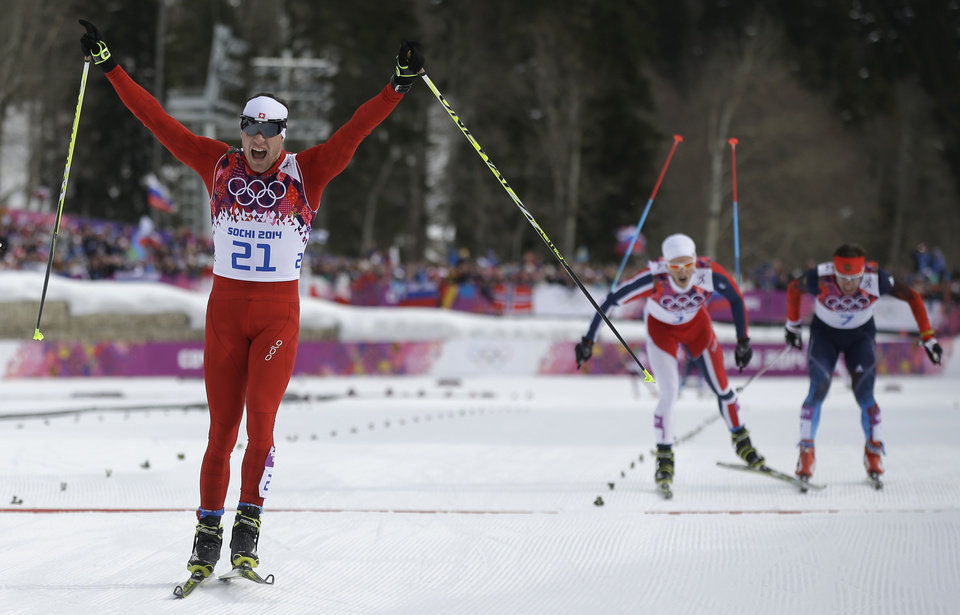 Photo - Switzerland's Dario Cologna celebrates winning the gold medal as Norway's Martin Johnsrud Sundby, second from right, and Russia's Maxim Vylegzhanin are to cross the finish line during the men's cross-country 30k skiathlon at the 2014 Winter Olympics, Sunday, Feb. 9, 2014, in Krasnaya Polyana, Russia. (AP Photo/Gregorio Borgia)