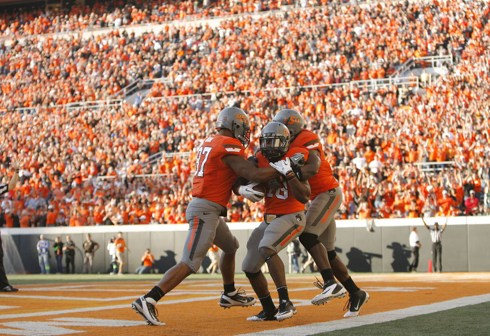 Photo - Oklahoma State's Tracy Moore (87) and Justin Blackmon (81) celebrate a touchdown with Herschel Sims (18) during a college football game between the Oklahoma State University Cowboys (OSU) and the Baylor University Bears (BU) at Boone Pickens Stadium in Stillwater, Okla., Saturday, Oct. 29, 2011. Photo by Sarah Phipps, The Oklahoman