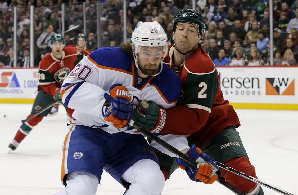 Photo - Minnesota Wild defenseman Keith Ballard (2) holds Edmonton Oilers left wing Luke Gazdic (20) off the puck during the second period of an NHL hockey game in St. Paul, Minn., Tuesday, March 11, 2014. (AP Photo/Ann Heisenfelt)