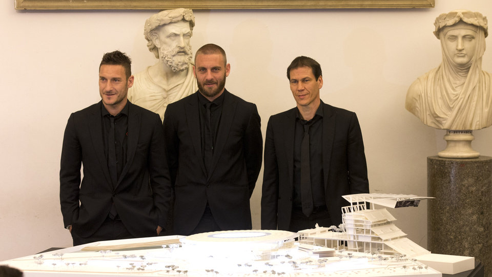 Photo - From left, Roma's Francesco Totti, Daniele De Rossi and coach Rudi Garcia pose on the occasion of the presentation of the new Roma soccer stadium, at Rome's Capitol Hill, Wednesday March 26, 2014. Three-time Serie A champion Roma has revealed plans to build a new privately financed stadium on the outskirts of the Italian capital. Labeled