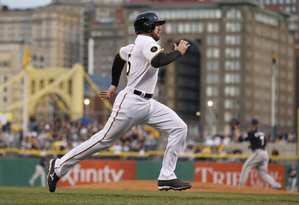 Photo - Pittsburgh Pirates' Ike Davis heads home to score from second on a hit by Neil Walker as Milwaukee Brewers first baseman Mark Reynolds, right, waits for the throw from center field in the second inning of a baseball game Saturday, April 19, 2014, in Pittsburgh. (AP Photo/Keith Srakocic)