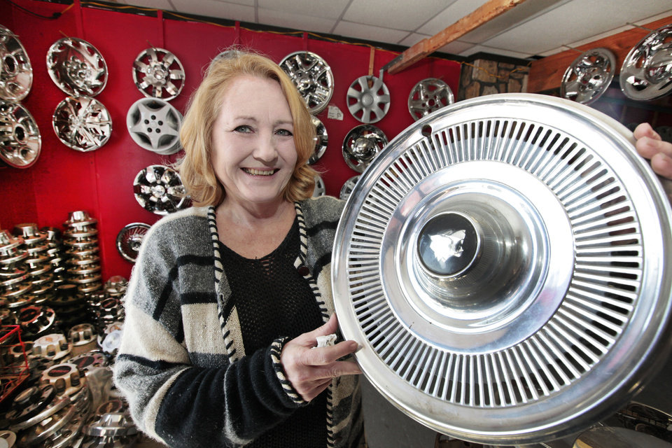 Sandra Mullins, who runs Hubcap World in Oklahoma City, is shown with a 1971 Buick Wildcat hubcap. PHOTO BY David McDaniel, The Oklahoman